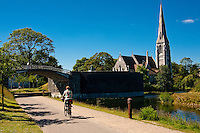 Bicyclist riding on a path near Saint Albans Anglican Church in Copenhagen, Denmark.