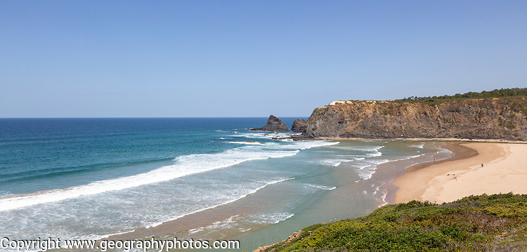 Atlantic Ocean waves breaking on rocky headland and bay with wide sandy beach, surfer and a few sunbathers, Praia de Odeceixe, Algarve, Portugal, Southern Europe