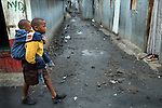 Mutava carrying Braise on his back through Marigoini slums on their way to school.<br />