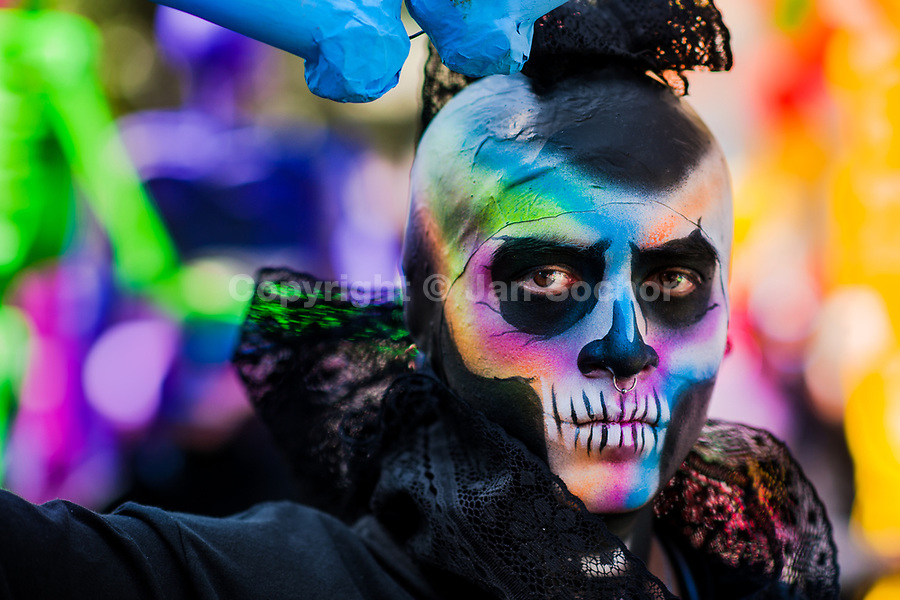 A Mexican man, having his face colorfully painted with skull, takes part in the Day of the Dead parade in Mexico City, Mexico, 29 October 2016. Day of the Dead (Día de Muertos), a syncretic religious holiday combining the death veneration rituals of the ancient Aztec culture with the Catholic practice, is celebrated throughout all Mexico. Based on the belief that the souls of the departed may come back to this world on that day, people gather at the gravesites in cemeteries praying, drinking and playing music, to joyfully remember friends or family members who have died and to support their souls on the spiritual journey.
