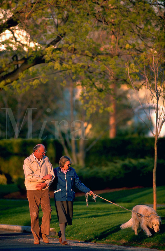 Older couple walking their dog.