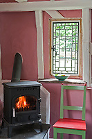 The cottage is full of junk-shop finds and salvage including the charming lead-paned window next to the wood-burning stove