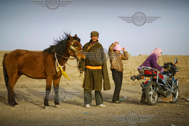 A semi-nomadic livestock farmer stands beside his horse.  Horses are the traditional form of transport but are being replaced by motorbikes.