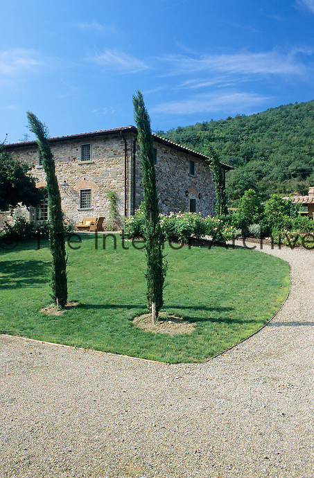 The driveway leading to this restored Tuscan farmhouse curves around a lawn housing two young cypress trees