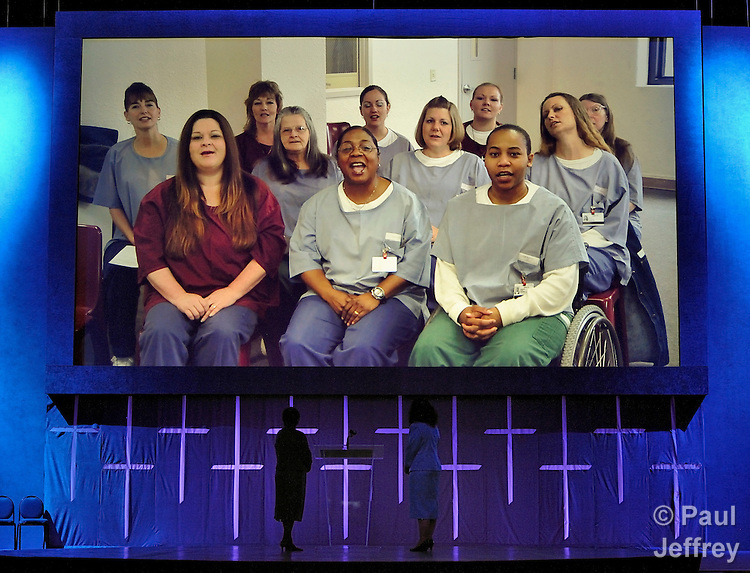 Inelda González (left) and Emily Innes greet a United Methodist Women's unit inside a penitentiary via live teleconferencing during the opening worship of the 2010 United Methodist Women's Assembly in St. Louis, Missouri.