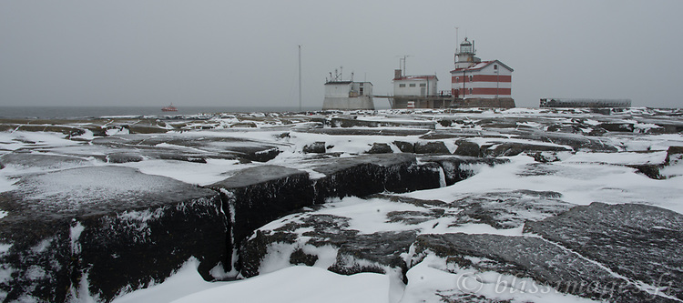 Snow and rock patterns on sleeting and overcast day in winter at Märket lighthouse in the Åland Sea of Finland.