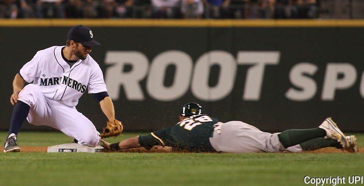 Oakland Athletics Eric Sogard (28) steals second base as Seattle Mariners shortstop Chris Taylor applies the late tag in the sixth inning September 13, 201 at Safeco Field in Seattle.  The Athletics beat the Mariners 3-2 when  Mariners pitcher Fernando Rodney  walked in Coco Crisp in the 10th inning. The game went 11 innings. UPI/Jim Bryant