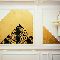 Graphic patterns, added to a simple palette of white, black and gold create an elegant combination as in this hand painted decoration on the white panelled walls