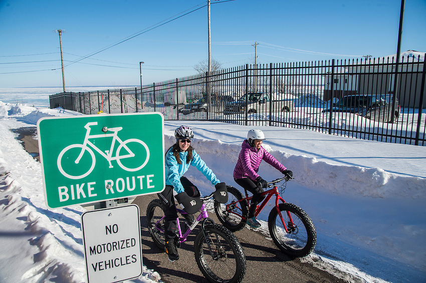 Winter cyclists on fat bikes ride the city bike path connecting downtown to the Lake Superior waterfront of Marquette, Michigan.