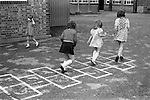 Primary school playground. Girls playing together. South London. 1970s Britain...