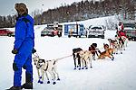 A handler holding a dog team ready to race. Knik 200 Sled Dog Race, Knik, Southcentral Alaska, Winter.