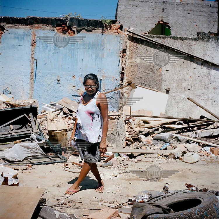 A woman stares at rubble in the Largo do Tanque favela. Residents of Largo do Tanque have undergone forced evictions and the demolition of their homes in to make room for the Transcarioca Highway, that will eventually be built to accommodate the 2016 Olympics. In less than two weeks, 54 houses were demolished with sledgehammers and bulldozers. The city assessor sent to handle negotiations told residents not to speak with one another or seek legal advice otherwise he would reduce settlement offers. Many residents agreed to compensations of around BRL 7000 (USD 3500).