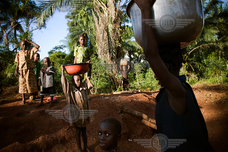 Women and children carry water from a well in buckets on their heads .