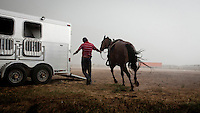 A man leads a horse into a trailer box during a storm at a local race meeting in Dodge CIty, Kansas. Horse racing is a favourite past time of many of the Hispanic migrant workers who have come to the area to work in its meat packing plants.