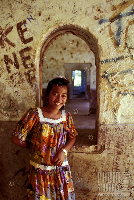 A local woman wearing a colorful dress smiles inside an old Japanese World War II grafitti covered hospital, now used for storage in copra production in Truk, Micronesia.