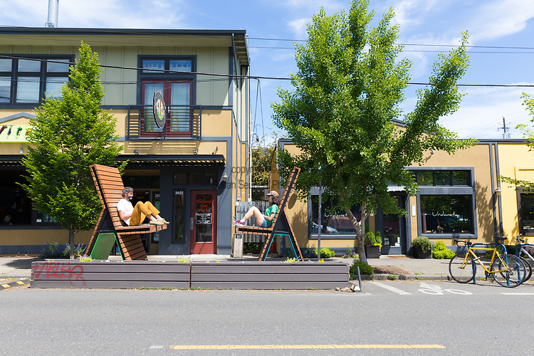 Two people enjoy oversized chairs in the NE Alberta Arts Neighborhood, Portland, OR, USA