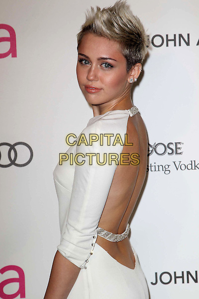 Miley Cyrus (wearing Azzaro).The 21st Annual Elton John AIDS Foundation Academy Awards Viewing Party held at The City of West Hollywood Park in West Hollywood, California, USA..February 24th, 2013.oscars half length dress white long side backless straps chains sleeves diamond side spiked platinum quiff dark buzzed roots hair dyed blonde   .CAP/ADM/KB.©Kevan Brooks/AdMedia/Capital Pictures.