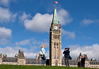 Tourists take photos of the Parliament in Ottawa Monday September 27, 2010. Parliament Hill (colloquially The Hill, in French: Colline du Parlement) is an area of Crown land on the southern banks of the Ottawa River in downtown with a Gothic revival suite of buildings, the parliament buildings, that serves as the home of the Parliament of Canada and contains a number of architectural elements of national symbolic importance.<br /> <br /> PHOTO :  Francis Vachon - Agence Quebec Presse