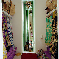 The narrow alcove in this walk-in wardrobe is lined with a full length mirror