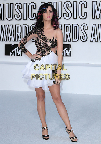 KATY PERRY .2010 MTV Video Music Awards held at the Nokia Theatre L.A. LIVE,  Los Angeles, California, USA, .12th September 2010..VMAS Arrivals full length beige black lace one sleeve dress white flesh tone mesh tiered layered ruffle sandals stars silver hand on hip .CAP/ADM/KB.©Kevan Brooks/AdMedia/Capital Pictures.
