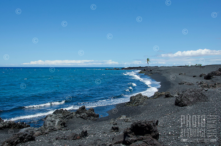A lone palm tree seems to stand guard over Keawaiki Bay and its mostly black sand beach, Hawai'i Island; an 1859 Mauna Loa eruption overflowed into this area, which was also the site of an ancient Hawaiian settlement and heiau (or temple).
