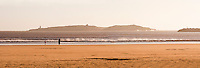 Panoramic photo of Essaouira beach and Mogador Island, Morocco, North Africa. This panoramic photo shows a father and his daughter walking on Essaouira beach, with Mogador Island behind them.