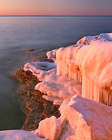 Winter sunset light on snow and ice patterns on Lake Michigan at Cave Point County Park; Door County, WI