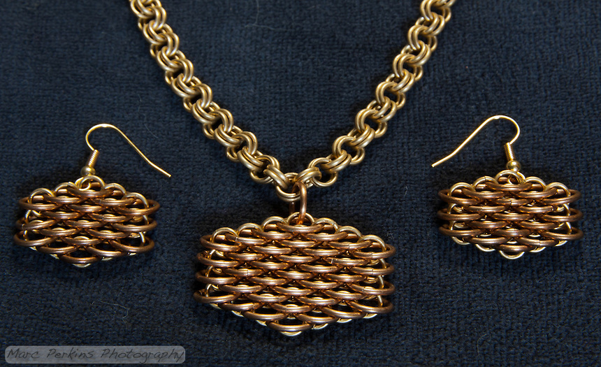 "A completed maille earring and necklace set that Michelle has titled ""Honeyscale"", as it makes her think of honey and bees.  The necklace is a simple double cable (4-in-2) weave made out of 19 gauge 5/32"" ID brass.  The earrings and pendant are both dragonscale weave made out of 18 gauge 1/4"" ID bronze and 19 gauge 5/32"" ID brass.  I love how they're glowing in this picture, thanks to diffused sunlight illuminating them from above."