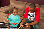Two year old toddler boy with father playing musical instrument drum set