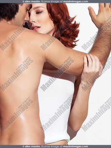 Closeup of a sexy young man with bare torso about to kiss a young red-haired woman