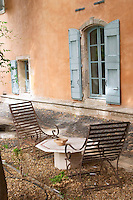 Prieure de St Jean de Bebian. Pezenas region. Languedoc. The villa. Window. Lounging chairs, garden furniture. In the garden. France. Europe.