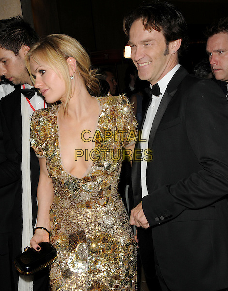 ANNA PAQUIN & STEPHEN MOYER.Leaving the 67th Golden Globes held at The Beverly Hilton Hotel in Beverly Hills, California, USA..January 17th, 2010 .departures half length couple gold beads beaded dress clutch bag black tuxedo couple plunging neckline globe cleavage .CAP/DVS.©Debbie VanStory/Capital Pictures