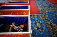 Trongduangtum Pratchaneeyaporn, a 36 year old business woman lays in a coffin during a religious ceremony at Wat Prommanee temple in Nakhon Nayok province May 28, 2011. Trongduangtum lays in the coffin once every week for the past three years as a part of the temple's unusual daily resurrection service after the first visits solved her financial problems and saved her from a car crash. Hundreds of Thai believers pay small fee to lay in nine pink coffins at 9:09 an and 1:09 pm every day in Wat Prommanee temple during a ritual that they believe will wash away bad luck and prolong life.      REUTERS/Damir Sagolj (THAILAND)