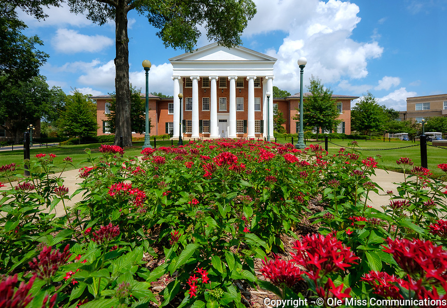 The Lyceum is framed between a blue sky and red flowers. Photo by Robert Jordan/Ole Miss Communications