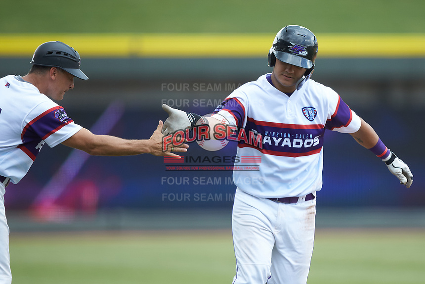 Winston-Salem Rayados manager Omar Vizquel (13) slaps hands with Daniel Gonzalez (17) as he rounds third base after hitting a home run against the Potomac Nationals at BB&T Ballpark on August 12, 2018 in Winston-Salem, North Carolina. The Rayados defeated the Nationals 6-3. (Brian Westerholt/Four Seam Images)
