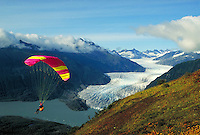 A parasailer rides the thermal winds off Thunder Mountain in the Tongass National Forest, in view of the Mendenhall Glacier and Lake, Juneau, Alaska in Southeast Alaska. Juneau Alaska, Mendenhall Glacier Recreation Area.