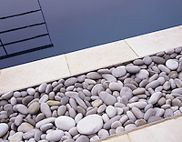 Detail of swimming pool with pebble and sandstone edging and the railing reflected in the water