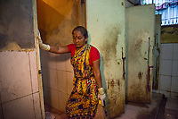 Bangladesh, Khulna, Sonadanga sweeper colony. Most of these people living in this slum are Dalit Hindu, or the untouchable caste working as sweepers and toilet cleaners. There are about 5.5 million Dalit across the country, they are most neglected caste in their society.  Jhorna Das works in fecal sludge management, cleaning toilets. Here she's cleaning toilets in the early morning in the public marketplace. The NGO, SNV, works to educate cleaners to have better hygiene when cleaning by washing hands, using rubber gloves and protection. Model released.