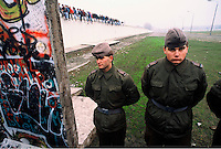 "East German Border Guards look through a newly opened section of the Berlin Wall a few days after the opening of the Wall on November 9, 1989.  In the background is the former ""death strip"", or no-man's land, between segments of the Wall that was almost impossible to cross. On the top of the Wall are celebrating East and West Germans who would have been shot only a few days before. The side facing East remains white while the West facing side is covered in graffiti. A caption reads ""Walls exist just to be pulled down.""."