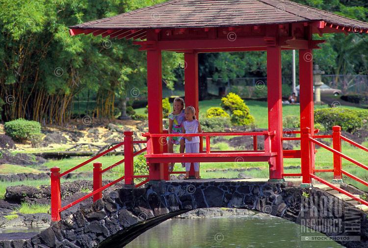 Two young girls under pagoda bridge at Liliuokalani park, Hilo, Big island