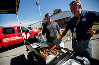 NWA Democrat-Gazette/JASON IVESTER <br /> Tyson Foods employees Derek Burleson (left) and Pat Bourke grill hotdogs on Wednesday, Sept. 23, 2015, at Frisco Park in downtown Rogers. Tyson has contribued to 100 million pounds of food since 2000 to hunger relief and announced on Wednesday their pledge to contribute $50 million in cash and product over the next five years.