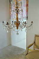 A crystal chandelier hangs low over a Louis XVI chair