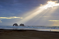 Person walking on beach with arch. Rockaway Beach. Oregon