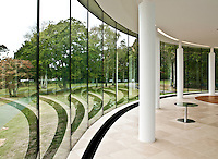 Reflections of the interior of the pool house create swirling patterns in the glass panes of the wall