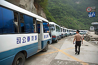 Man searching among a row of tourist buses parked on Mount Hua, one of China's five Sacred Taoist Mountains, in Shaanxi, China.