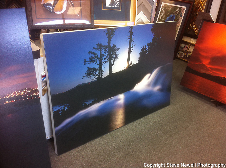 """Shadow Moon"" Eagle Falls- Emerald Bay Lake Tahoe, CA. This is a full moon rising over the Lake Tahoe Basin on May 5th, 2012. This is a photo of one of my giclee prints on canvas at the frame shop. I specialize in large oversize landscapes. This image was taken at 8:51pm.  I used a 30 second exposure, f8.0 aperture, ISO 400, 21mm lens.  It was my first time using my Canon 5D Mark ll and I wanted to capture the moon lighting up the basin with the water in motion using a longer exposure. This image has the shadow of the trees casting across the waterfall. On the left side you can see the lights on Kingsbury Grade and a car's light trail through the tree line on Emerald Bay Rd.  Shadow Moon is a special moment in time captured at Emerald Bay. The detail of everything stationary is spot on with the waterfall flowing and glowing."