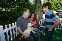 NWA Democrat-Gazette/BEN GOFF @NWABENGOFF<br /> Christopher Gardner, wife Tamy (CQ) Gardner and son Daniel Gardner, 12, of Bentonville pet the puppy they chose to adopt Thursday, May 4, 2017, at the Pedigree Puppy Village at Compton Gardens during the Bentonville Film Festival. Animal rescue groups from Northwest Arkansas will have puppies up for free adoption at the Puppy Village throughout the festival.