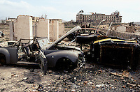 The remain of the Lincolm on the left, of the black&yellow Ford on the right and the bullet-proof Ziz 110 in the back of the destroy UNESCO bunker in the courtyard of he national museum of Afghanistan, in Spring 1995. On the back left, the burn and loot national museum and on the right, the destroy Darulaman Palace.