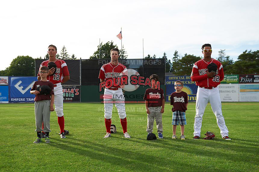 """Batavia Muckdogs Corey Bird (12), Aaron Knapp (5), and Jhonny Santos (32) stand for the national anthem with some """"Stars of the Game"""" participants before a game against the Brooklyn Cyclones on July 4, 2016 at Dwyer Stadium in Batavia, New York.  Brooklyn defeated Batavia 5-1.  (Mike Janes/Four Seam Images)"""