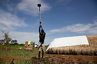 """Amule Kamba, father of 5, prepares the area around his tent for  cultivation. """"i left Congo in March after the LRA captured some of my chief's children. I hear that the LRA are still  attacking in my  area..I will stay here until they finish,"""" he said."""